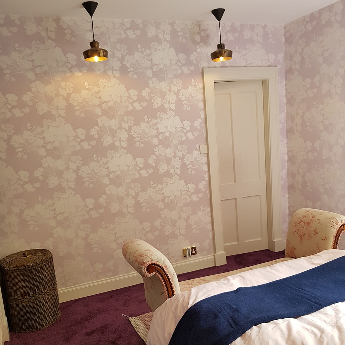 pink flower wall paper, tom dixon pendants, antique ottoman blue throw on bed