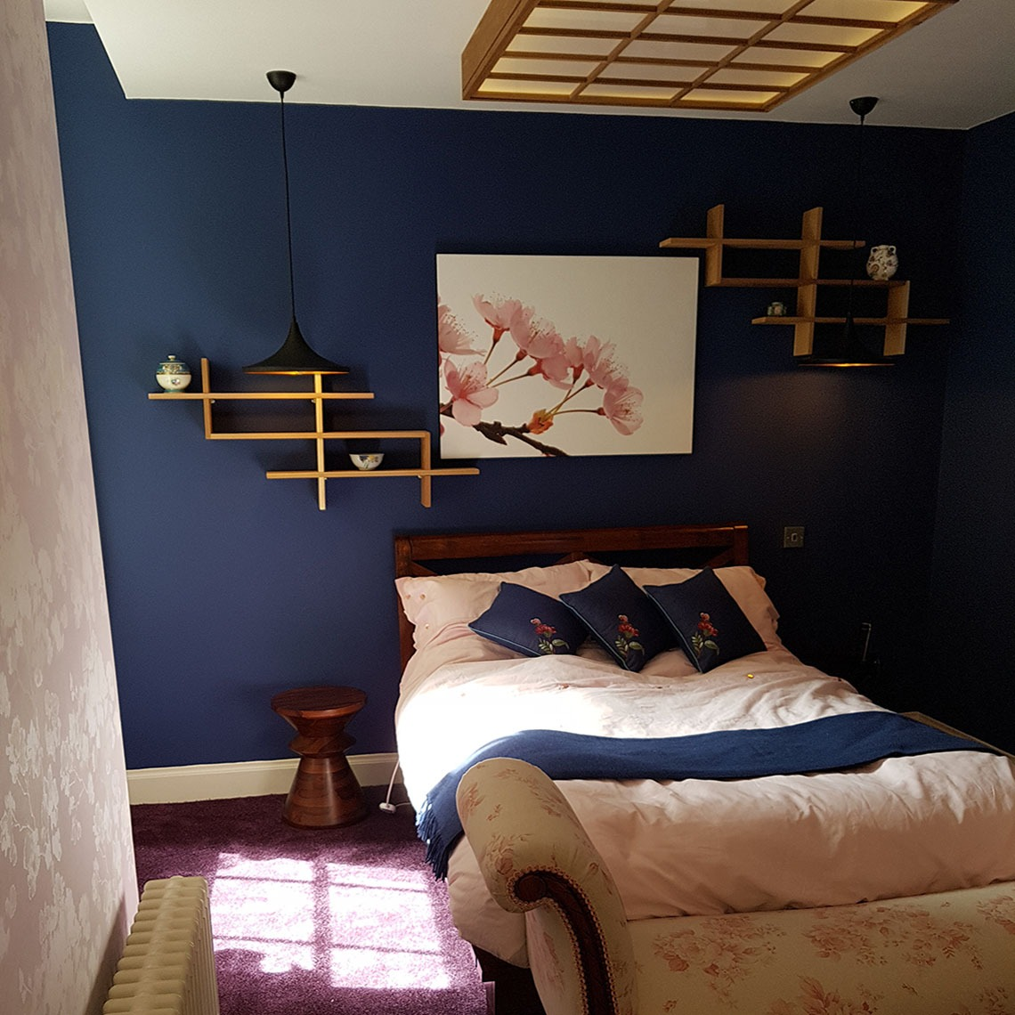 blue wall with pink flower artwork, tom dixon pendants and soji ceiling light