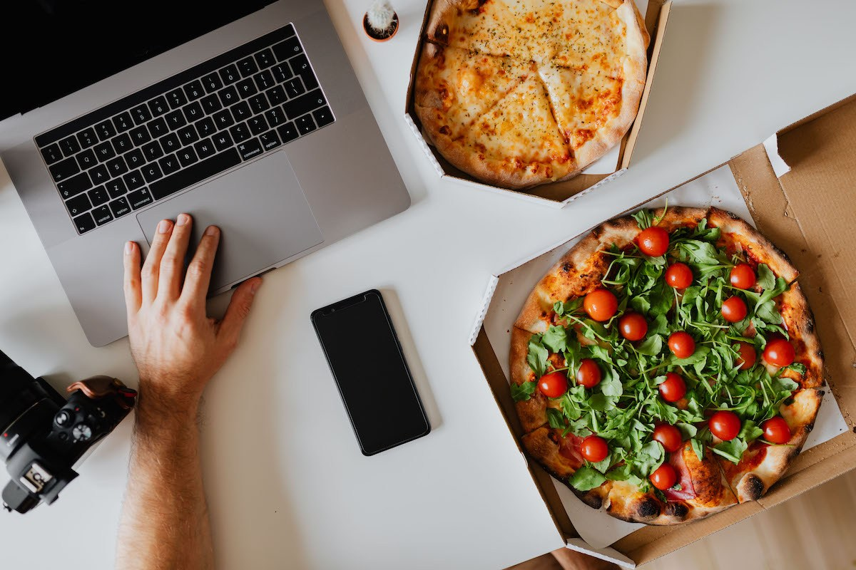 Laptop and pizza on desk