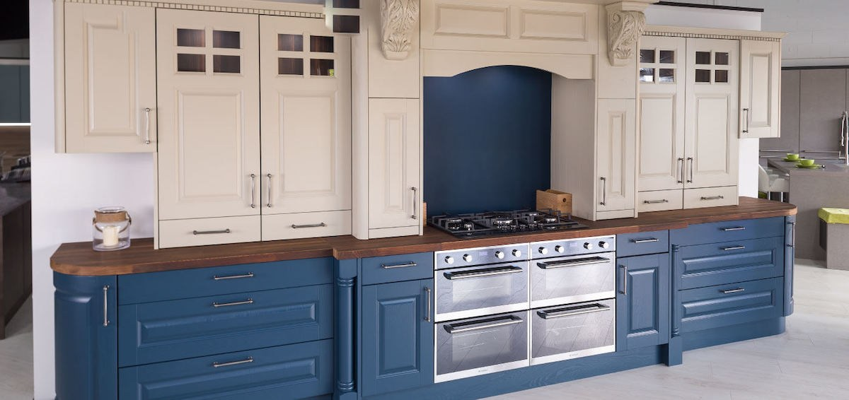 traditional kitchen with blue and white cabinets, and dark oak top counter